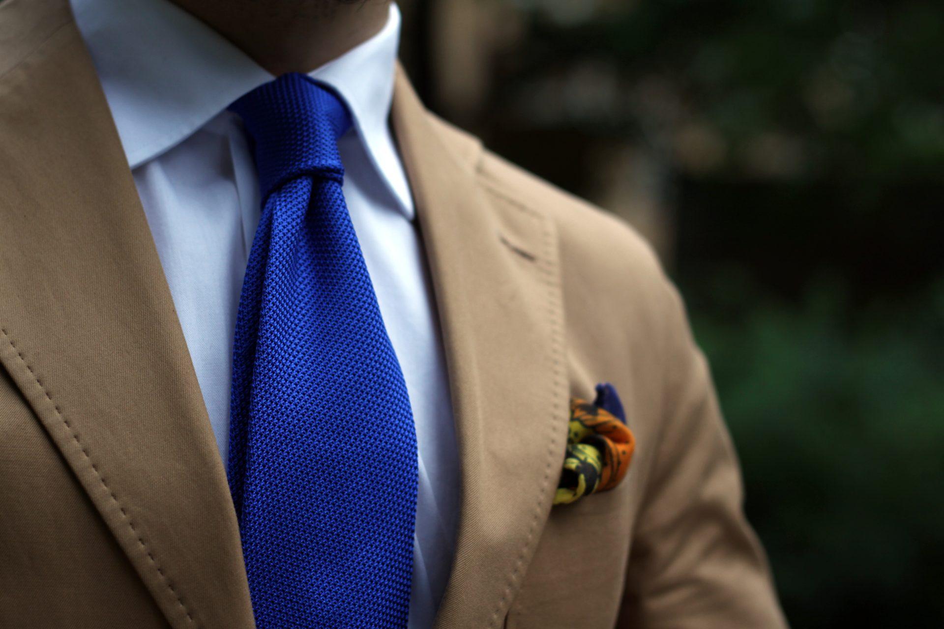 Sininen grenadiinisolmio ja kuviollinen taskuliina