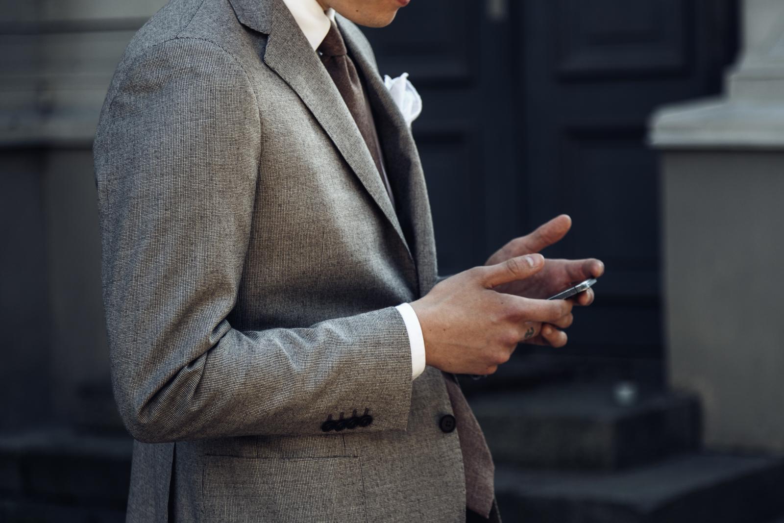 Ruskea pukua, valkoinen paita ja solmio.